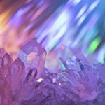 Sparkling multi-colored background with rays of light and crystals of rock crystal.